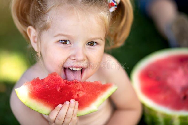 Sluit omhoog Portret van een jong blondemeisje met watermeloen, de zomer openlucht Gezonde snack voor kinderen stock foto's