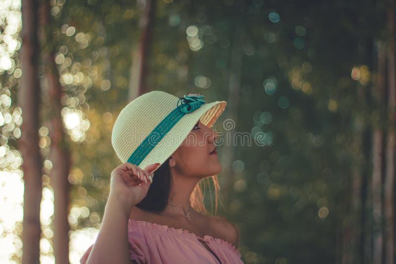 Sluit omhoog portret van een jong meisje die een witte zonhoed en een bos dragen als achtergrond royalty-vrije stock fotografie