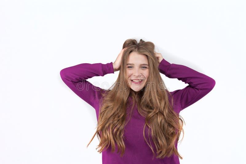 Sluit omhoog portret van een jong positief, glimlachend meisje in vrijetijdskleding dat zacht haar haar raakt Natuurlijke, gezond royalty-vrije stock afbeelding
