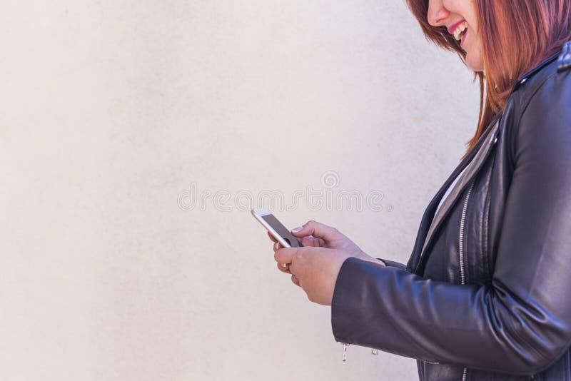 Sluit omhoog portret van een jonge mooie vrouw die op haar mobil typen stock foto