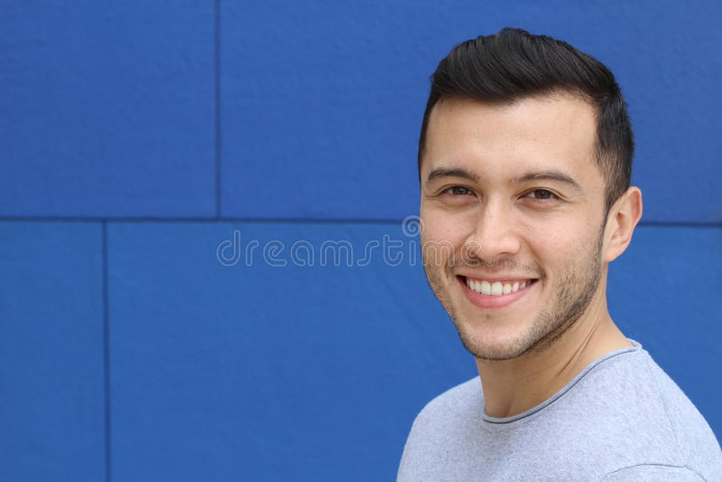 Sluit omhoog portret van een jonge Spaanse tienermens die camera met een blije het glimlachen uitdrukking, tegen een blauwe achte stock foto's