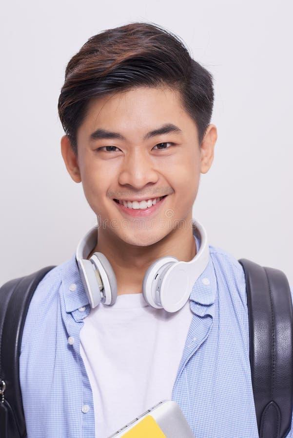 Sluit omhoog portret van een knappe jonge Aziatische mens die op isola glimlachen stock afbeeldingen