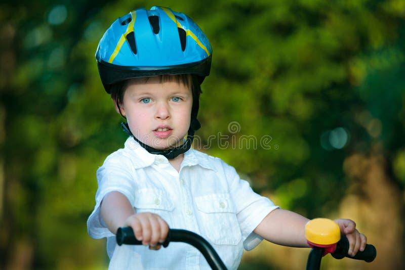 Sluit omhoog portret van een leuke kleine jongen op fiets stock fotografie