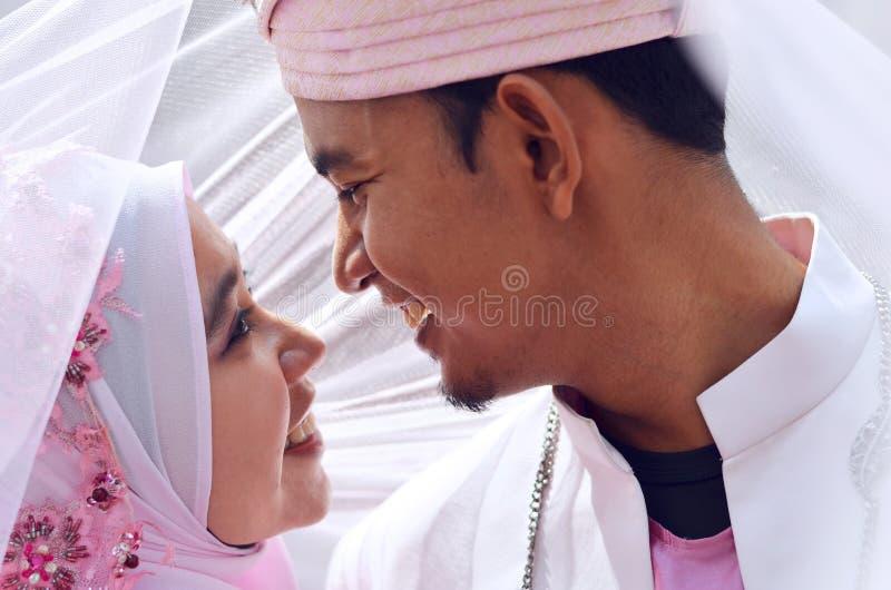 Sluit omhoog portret van een malay bruid en een bruidegom onder sluier met mooie emotie stock afbeeldingen