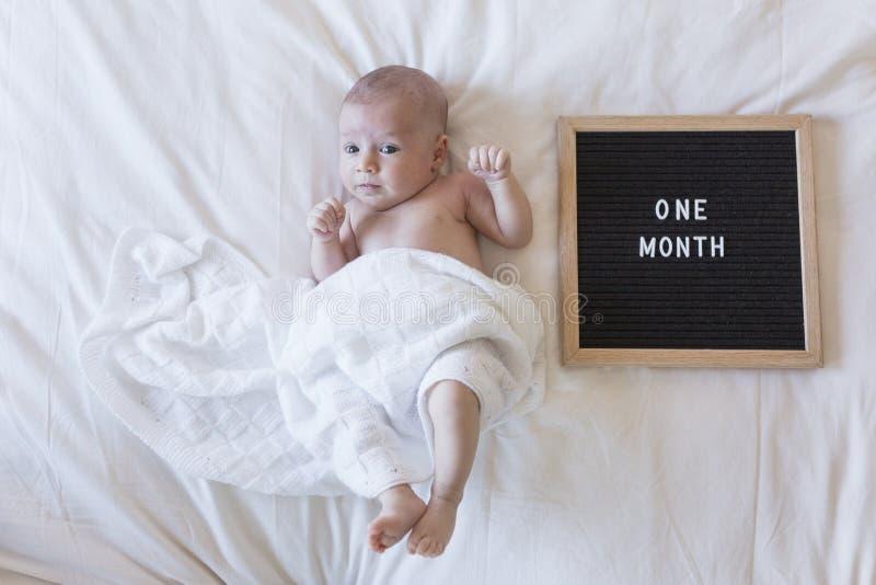 sluit omhoog portret van een mooie baby op witte achtergrond thuis met een uitstekende brievenraad met bericht: één maand royalty-vrije stock afbeelding