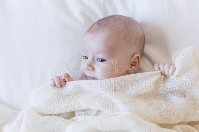 sluit omhoog portret van een mooie baby op witte die achtergrond thuis met een deken wordt behandeld stock afbeelding