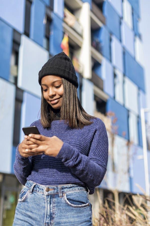 Sluit omhoog portret van een mooie jonge Afrikaanse vrouw in openlucht gebruikend cellphone in de stad stock foto's