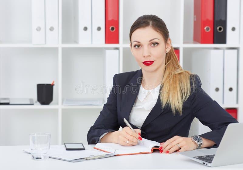 Sluit omhoog portret van een mooie jonge bedrijfsvrouw die en de camera glimlachen bekijken royalty-vrije stock foto's