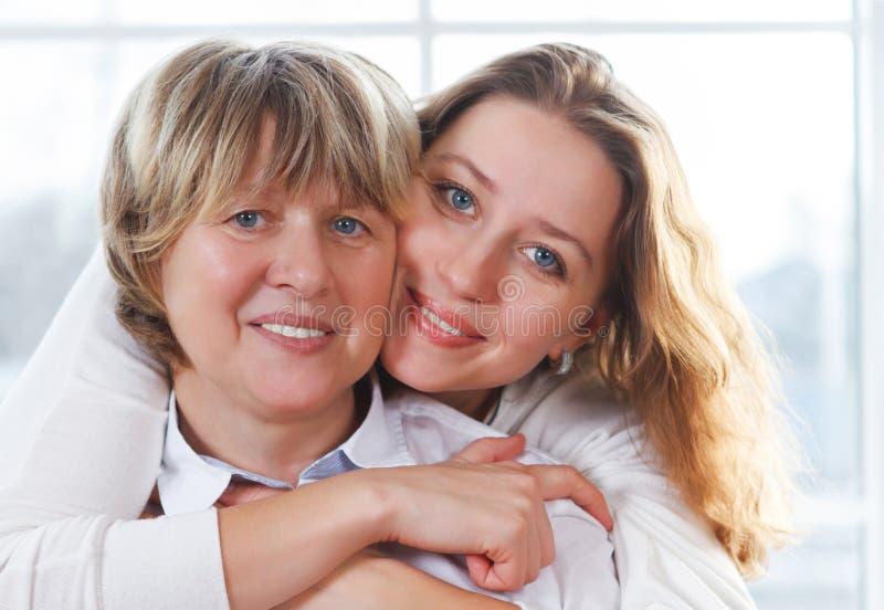 Sluit omhoog portret van een rijpe moeder en een volwassen dochter die cl zijn royalty-vrije stock foto's