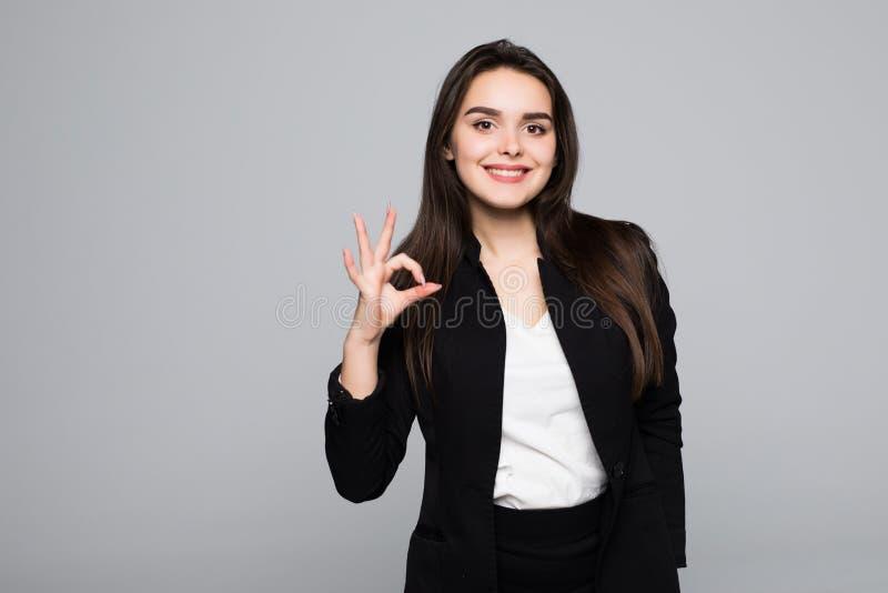 Sluit omhoog portret van een vrolijke jonge bedrijfsvrouw die o.k. die gebaar tonen over grijze achtergrond wordt geïsoleerd stock fotografie