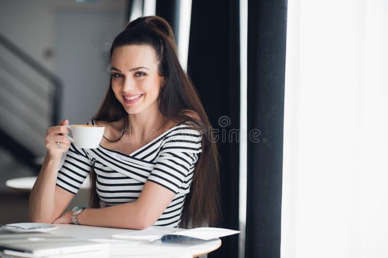 Sluit omhoog portret van een vrouwenzitting dichtbij venster en holding een kop van koffie in een restaurant royalty-vrije stock foto