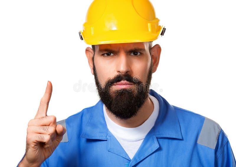 Sluit omhoog portret van gebaarde bouwer in bouwvakker, voorman of geïsoleerde hersteller in de helm die vinger tonen, royalty-vrije stock afbeeldingen