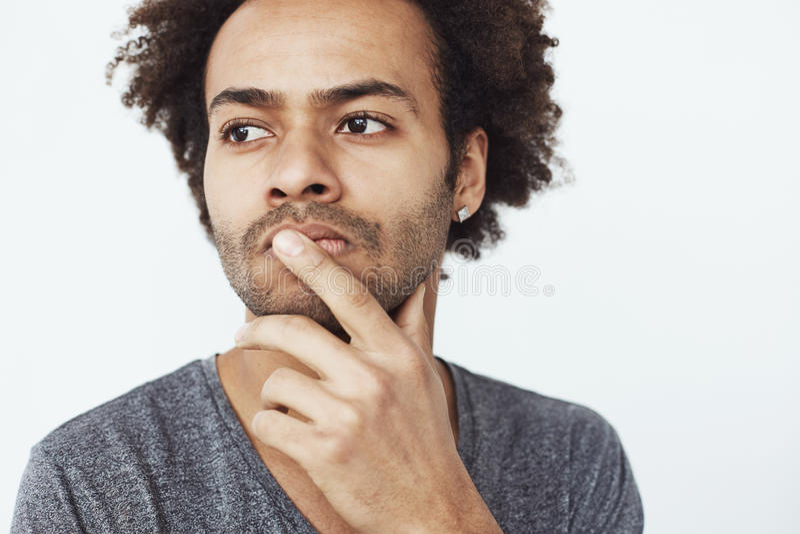 Sluit omhoog portret van geconcentreerd ernstig Afrikaans mannetje die over afgelopen en toekomstige plannen denken of dromend wa stock afbeelding