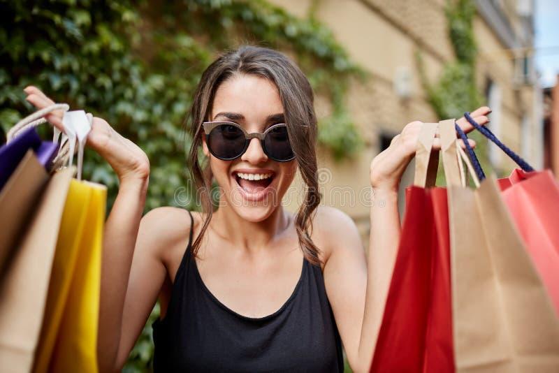 Sluit omhoog portret van gelukkige blije jonge donker-haired Kaukasische vrouw die in lusjeglazen en zwart overhemd in camera kij stock fotografie