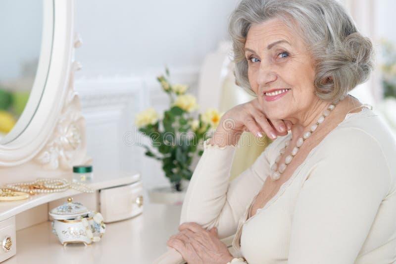 Sluit omhoog portret van gelukkige hogere vrouwenzitting dichtbij toilettafel stock foto's
