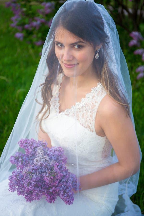 Sluit omhoog portret van gelukkige mooie bruid met lilac binnen bloemen royalty-vrije stock foto