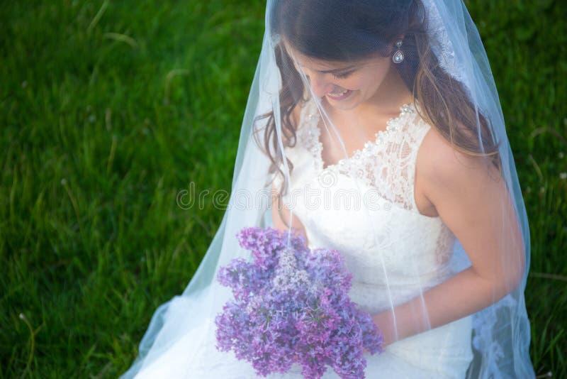 Sluit omhoog portret van gelukkige mooie bruid met lilac bloemen royalty-vrije stock afbeeldingen