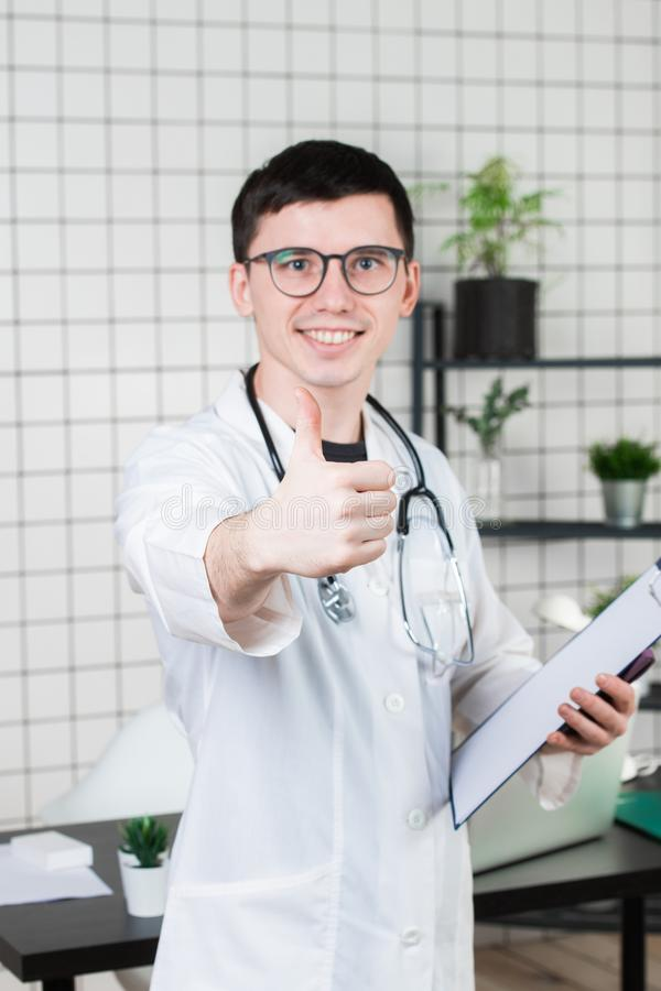Sluit omhoog portret van glimlachende arts die de nieuwe manier van behandeling adviseren door duim te tonen royalty-vrije stock foto