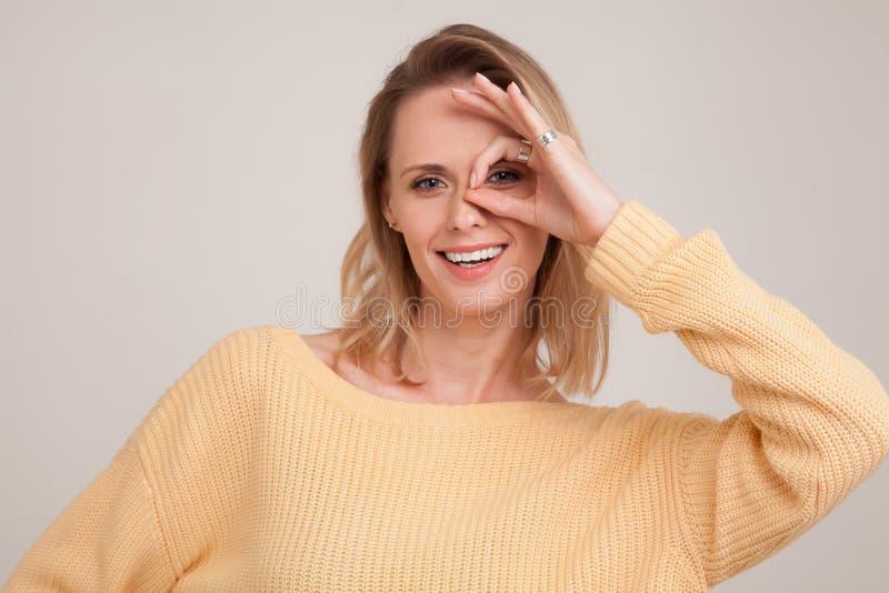 Sluit omhoog portret van glimlachende blondevrouw die met witte tanden, de camera door vingers in o.k. gebaar bekijken Geel drage royalty-vrije stock foto