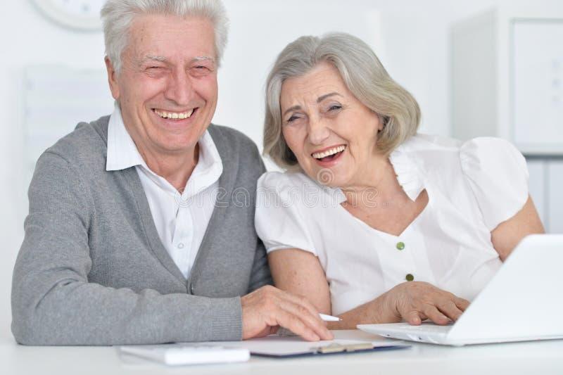 Sluit omhoog portret van glimlachende hogere mensen die met computer thuis werken stock foto