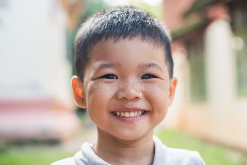 Sluit omhoog portret van het Aziatische jongen glimlachen in het park royalty-vrije stock afbeelding