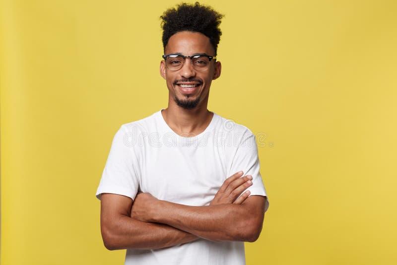 Sluit omhoog portret van het gelukkige Afrikaanse Amerikaanse die mens stellen met wapens op geïsoleerde gele achtergrond worden  royalty-vrije stock afbeeldingen