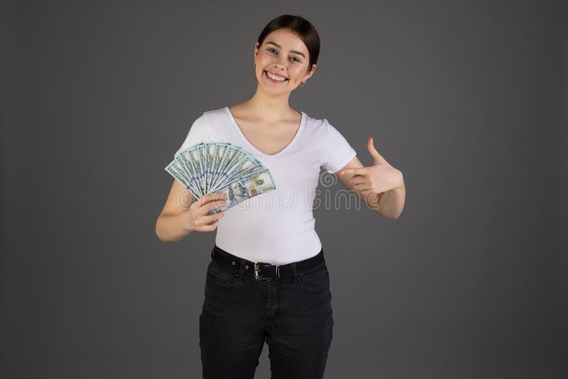 Sluit omhoog portret van het gelukkige eurupean geld van de vrouwenholding op grijze achtergrond stock fotografie