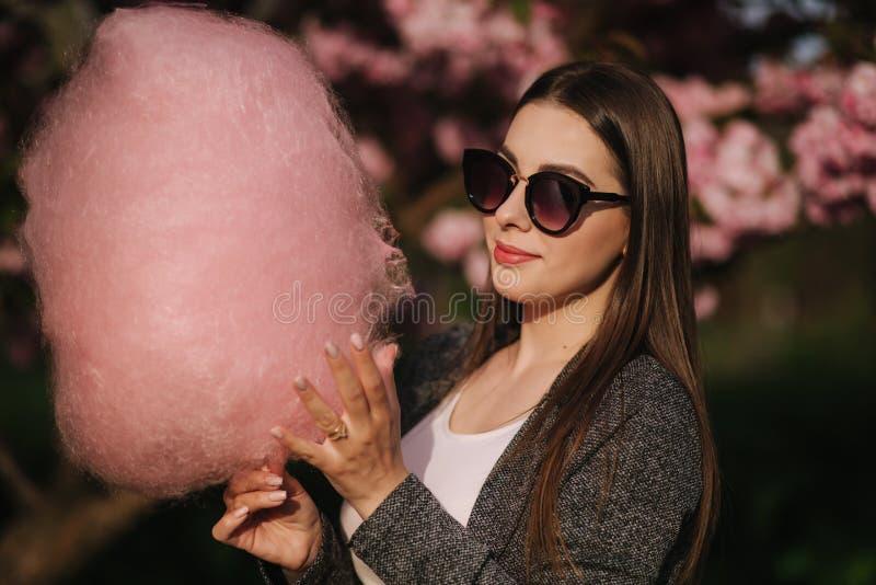 Sluit omhoog portret van het glimlachen van de gesponnen suiker van de meisjesholding in handen Het meisje kleedde zich in grreyb stock fotografie