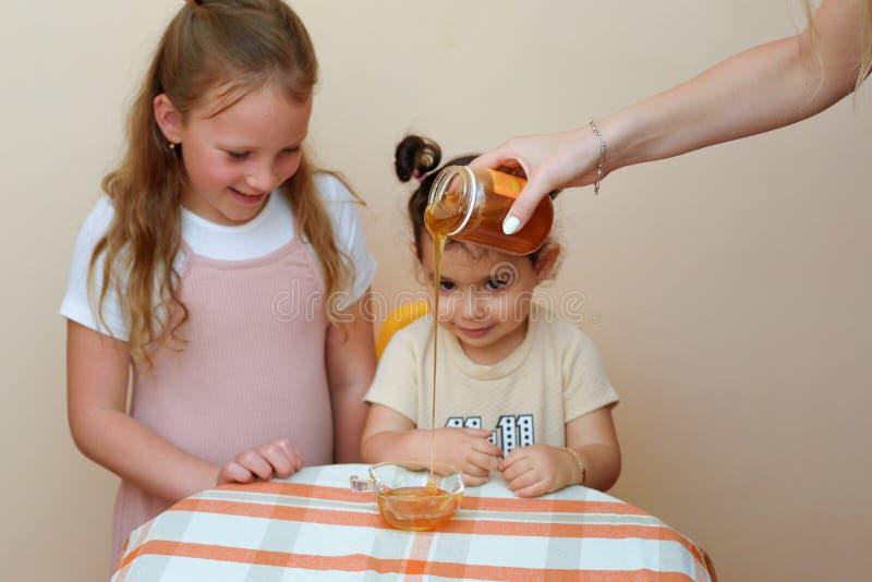 Sluit omhoog portret van het grappige leuke meisje twee kijken op vrouwenhand die verse honing van kruik gieten in kom stock foto's