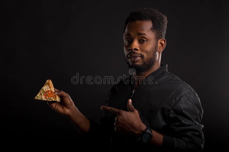Sluit omhoog portret van het jonge Afrikaanse stuk van de mensenholding van pizza stock afbeelding