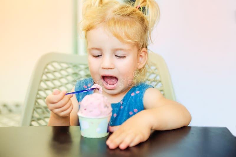 Sluit omhoog portret van het leuke blondy meisje die van de peuterbaby bessenroomijs van document kom in koffie eten Smaak en kin stock foto's
