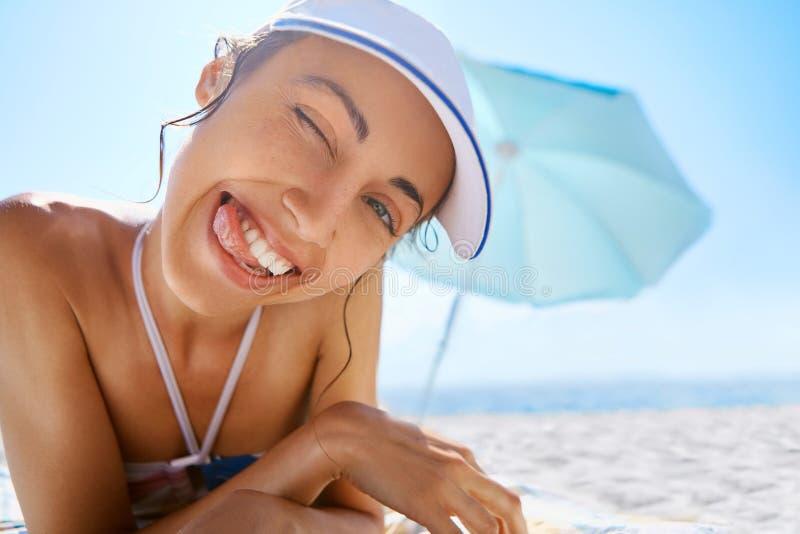 Sluit omhoog portret van het mooie het glimlachen gelukkige vrouw looien in wit GLB op zandig strand bij de zomer De vakantie van stock afbeelding