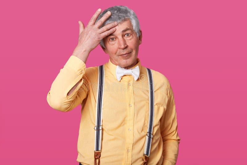 Sluit omhoog portret van het rijpe mens stellen met hand op voorhoofd geïsoleerd over roze achtergrond Het knappe oudere mens ste stock foto's