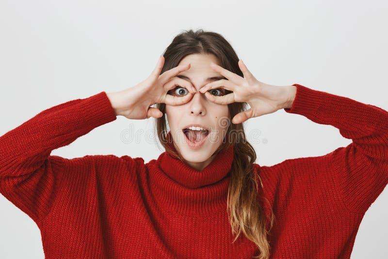 Sluit omhoog portret van jong gevoelsmeisje die beschermende brillen met handen imiteren, kijkend onderhouden en grappig, geïsole stock afbeelding