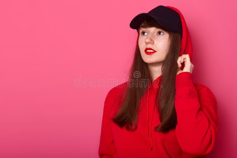 Sluit omhoog portret van jong leuk donkerbruin tienermeisje in toevallig rood hoodie en GLB, die met heldere listick op roze acht royalty-vrije stock fotografie