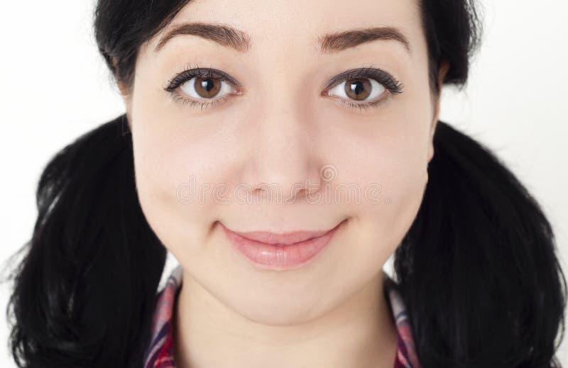 Sluit omhoog portret van jong meisje of vrouw met zwart die haar in twee vlechten wordt gebonden, glimlacht zij en vriendschappel stock foto's
