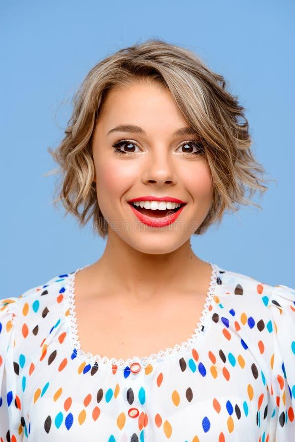 Sluit omhoog portret van jong mooi meisje over blauwe achtergrond stock afbeelding