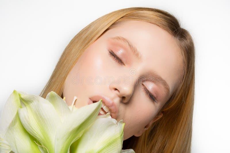 Sluit omhoog portret van jong vrouwelijk model met perfecte huid en gesloten ogen, het grote witte deel van de bloemdekking van g stock afbeelding