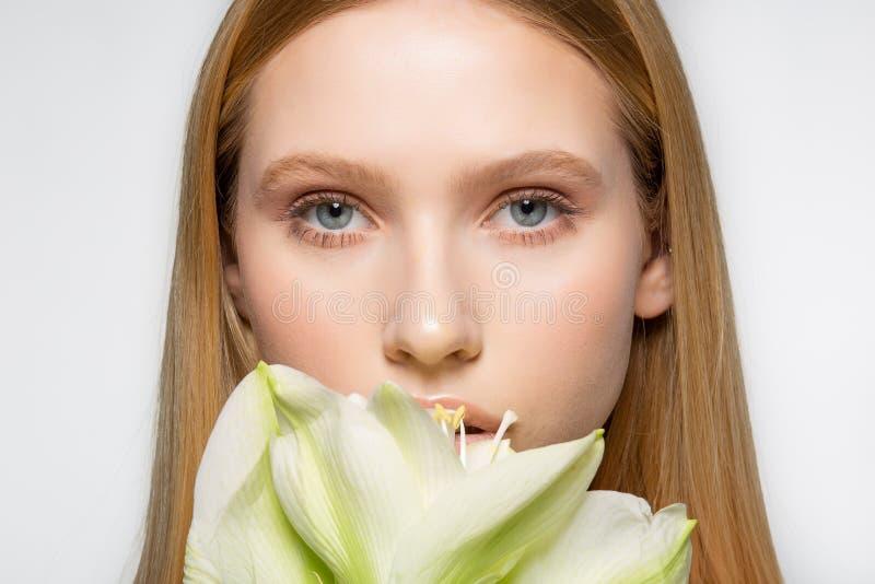 Sluit omhoog portret van jong vrouwelijk model met perfecte huid en mooie ogen, het grote witte deel van de bloemdekking van gezi royalty-vrije stock afbeeldingen