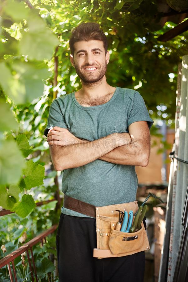 Sluit omhoog portret van jonge knappe gebaarde tuinman die met tuinhulpmiddelen die glimlachen, zich in bomenschaduw bevinden, kr stock foto
