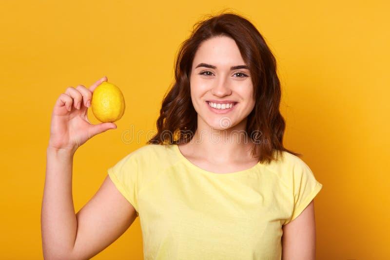 Sluit omhoog portret van jonge mooie donkere haired vrouw met toothy glimlach, die met in hand citroen stellen, direct bekijkend  stock foto's
