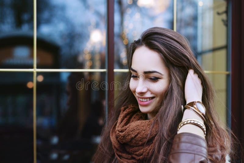 Sluit omhoog portret van jonge mooie glimlachende vrouw die modieuze kleren dragen die zich op de straat bevinden Het model neer  royalty-vrije stock afbeelding