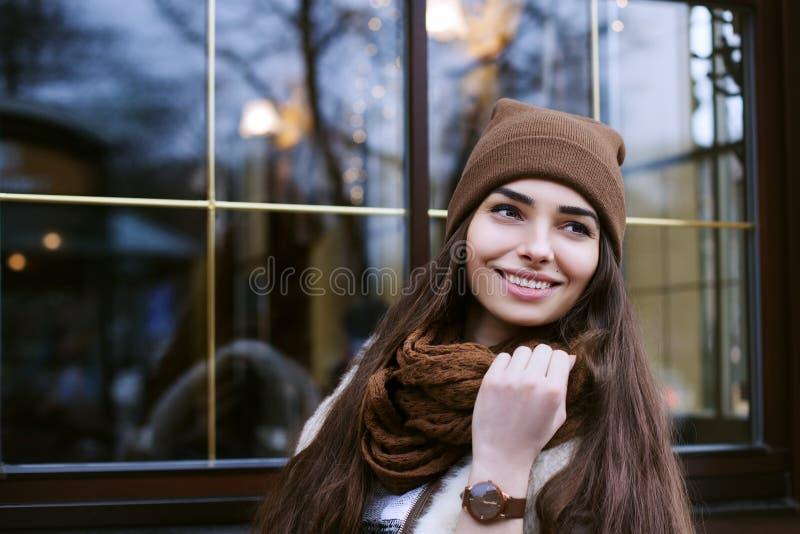 Sluit omhoog portret van jonge mooie glimlachende vrouw die modieuze kleren dragen die zich op de straat bevinden Het model opzij stock foto's