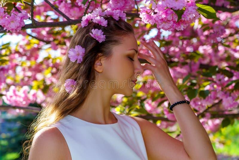 Sluit omhoog portret van jonge mooie vrouw met roze bloemen in haar haar is in witte kleding stelt offerte in de boom van bloesem royalty-vrije stock afbeeldingen