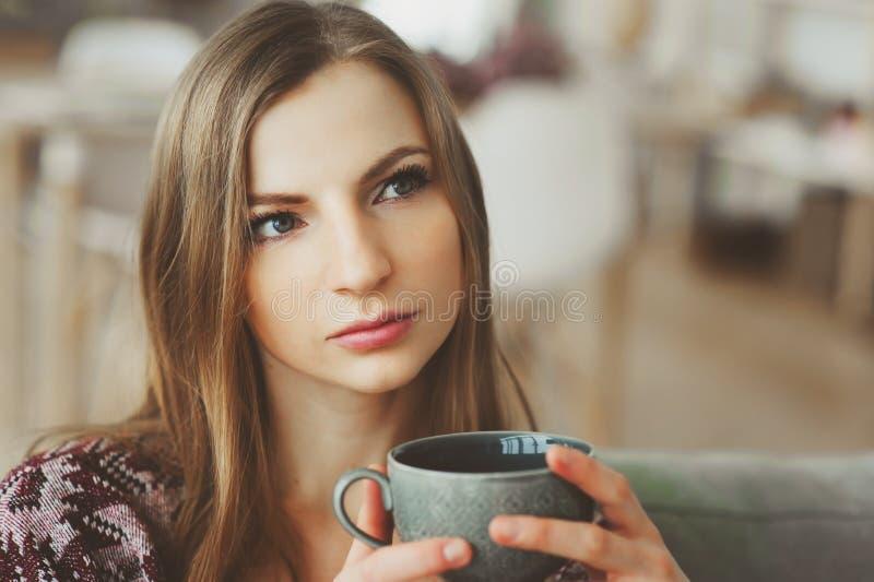sluit omhoog portret van jonge nadenkende vrouw met kop thee of koffie royalty-vrije stock afbeelding
