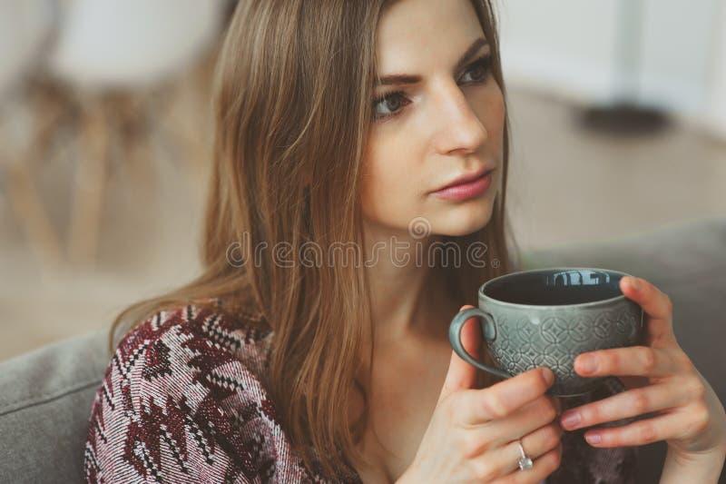 sluit omhoog portret van jonge nadenkende vrouw met kop thee of koffie stock foto