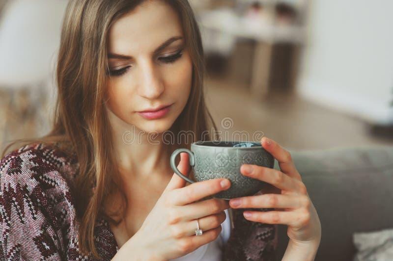 Sluit omhoog portret van jonge nadenkende vrouw met kop thee of koffie thuis alleen zittend stock afbeelding