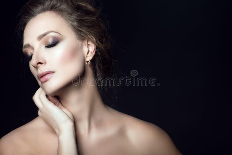 Sluit omhoog portret van jonge schitterende vrouw met updohaar en gesloten ogen wat betreft haar gezicht met haar hand royalty-vrije stock afbeelding