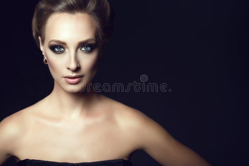Sluit omhoog portret van jonge schitterende vrouw met updohaar en perfectioneer maken recht omhoog het kijken stock fotografie
