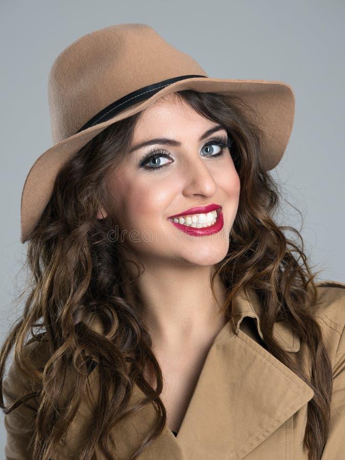 Sluit omhoog portret van jonge schoonheid met rode lippen en witte toothy glimlach dragend hoed stock fotografie